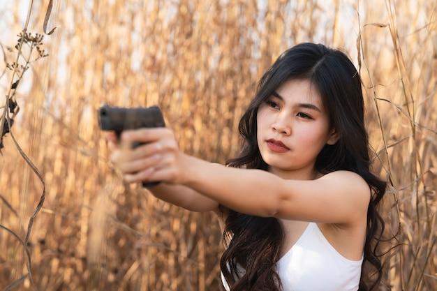 Piękna azjatka ma pistolet na suchej trawie
