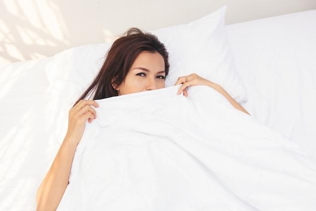 Piękna azjatka na łóżku, patrząc i zerkając na pościel zaskoczona.