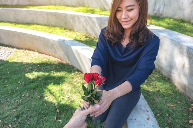 Piękna azjatka otrzymująca czerwone kwiaty róży od chłopaka w walentynki na świeżym powietrzu