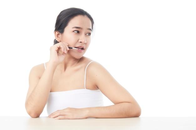 Piękna azjatka patrząc w kamerę iz małym pędzelkiem do kosmetyków podniosła dłoń do konturowania głowy brwi z odkrytymi ramionami na białej powierzchni