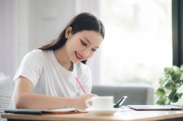 Piękna azjatka pisze i pracuje siedząc w salonie w domu.