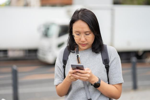 Piękna azjatka podróżnik używa do wyszukiwania smartfona w centrum miasta