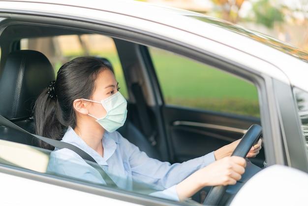 Piękna azjatka prowadząca samochód w masce na twarzy wychodząca na zewnątrz zachowaj zdrowie, chroniąca przed koronawirusem covid-19 epidemia choroby, światowa pandemia, emisja zanieczyszczeń powietrza