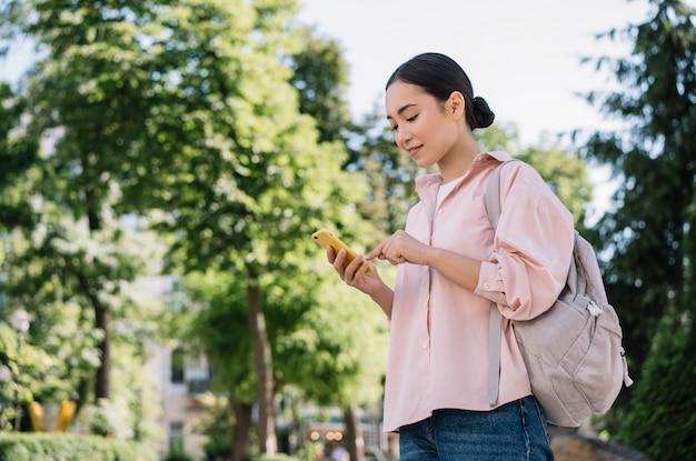Piękna azjatka przy użyciu telefonu komórkowego, spacery w parku