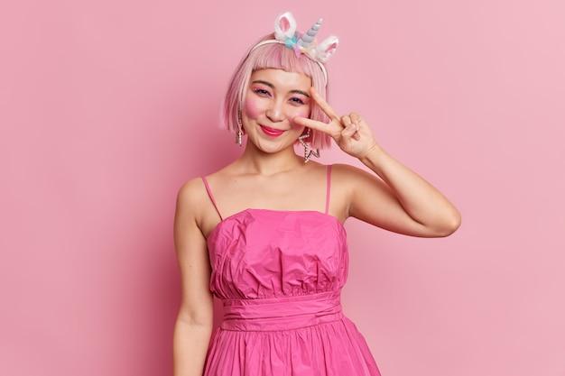 Piękna azjatka robi gest pokoju, uśmiecha się przyjemnie, nosi świąteczną sukienkę, bawi się na przyjęciu, pozuje na znak zwycięstwa
