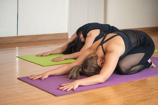Piękna azjatka robi joga ćwiczenia na relaks i medytację z trenerem w domu.