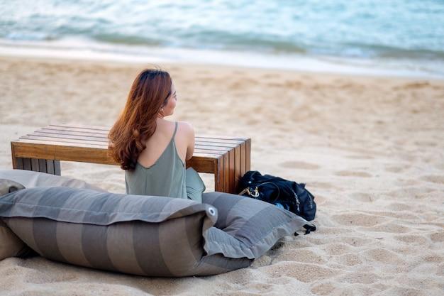 Piękna azjatka siedzi na plaży nad brzegiem morza