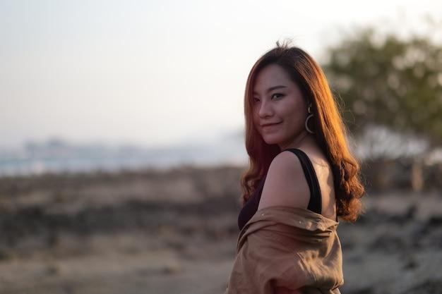 Piękna azjatka spaceru na plaży nad brzegiem morza
