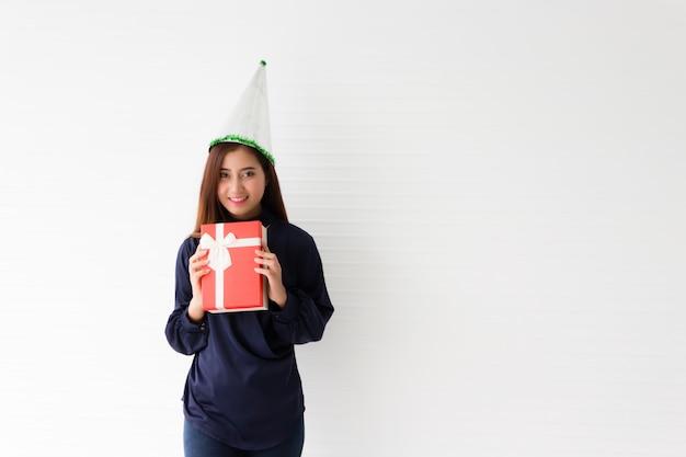 Piękna azjatka, tajka, ma na sobie granatową swobodną sukienkę i imprezowy kapelusz. nosi czerwone pudełko z uśmiechem i radosną miną.