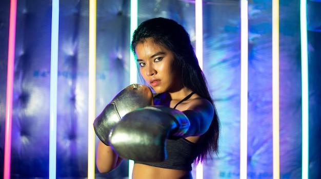 Piękna azjatka trenuje i uderza pięściami w srebrne złote rękawiczki z jednym palcem. office girl ćwiczy w nowoczesnej kolorystyce neon muay thai boxing gym z odrobiną wody potu