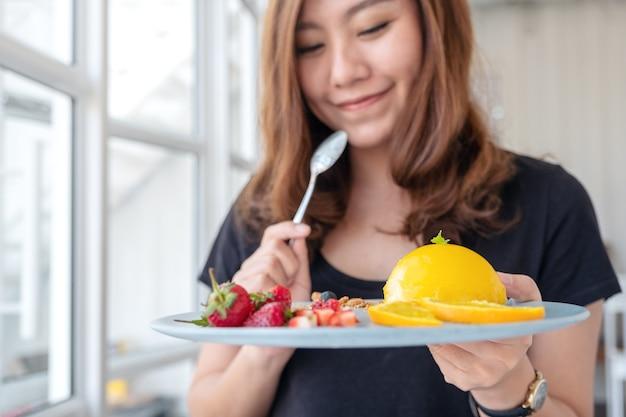 Piękna azjatka trzyma talerz pomarańczowego ciasta z mieszanymi owocami i łyżką w kawiarni