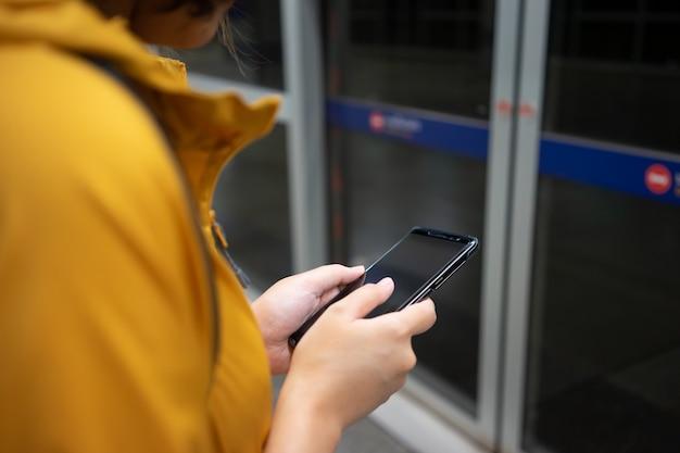 Piękna azjatka używa smartfona w centrum miasta do wyszukiwania różnych