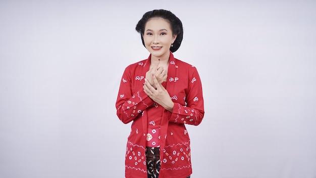 Piękna azjatka w kebaya pozuje elegancko na białym tle
