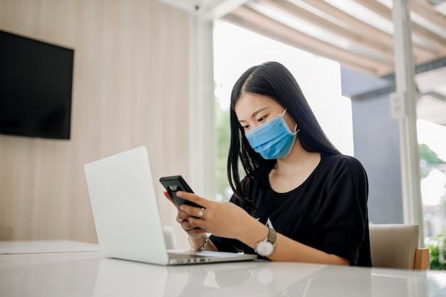 Piękna azjatka w masce i używająca smartfona w biurze do zapobiegania wirusowi covid-19.