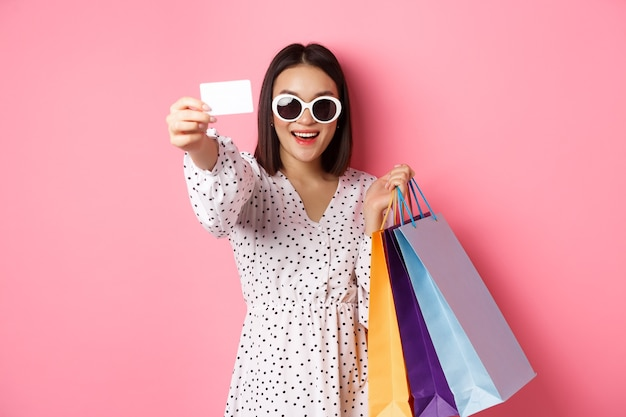 Piękna azjatka w okularach przeciwsłonecznych robi zakupy, trzyma torby i pokazuje kartę kredytową, stojąc na różowym tle