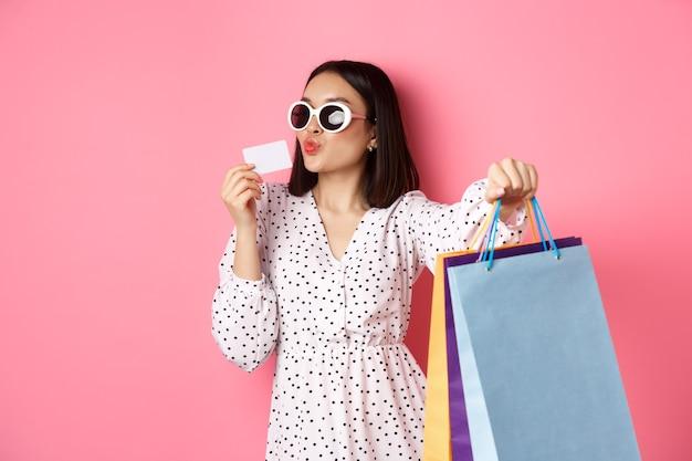 Piękna azjatka w okularach przeciwsłonecznych robi zakupy, trzymając torby i całując kartę kredytową, stojąc na różowym tle