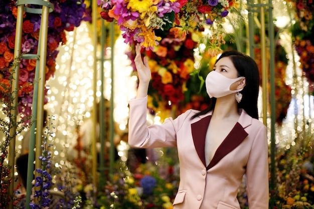 Piękna azjatka w różowym garniturze biznesowym relaksuje się w polu tysięcy kwiatów