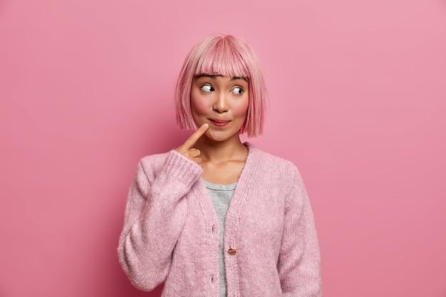 Piękna azjatka wygląda z zaskoczeniem i zaciekawieniem po prawej stronie, trzyma palec wskazujący przy ustach, ma ufarbowane na różowo włosy, modelki w domu, ubrana w wygodny sweter. rozważna, urocza dama