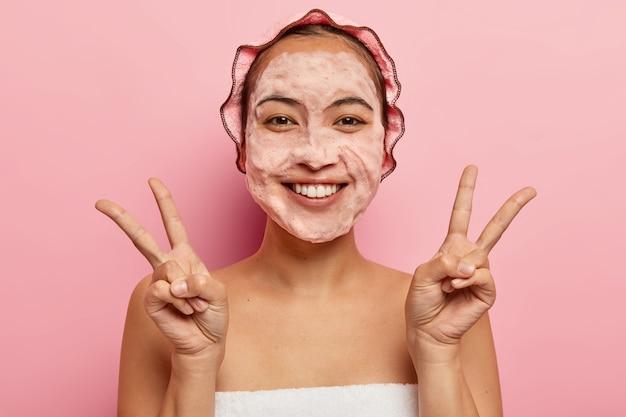 Piękna azjatka wykonuje gest pokoju obiema rękami, uśmiecha się pozytywnie, myje twarz mydłem bąbelkowym, dba o higienę, cieszy się świeżością po kąpieli