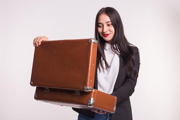 Piękna azjatka z czerwonymi ustami wpatrując się w walizkę retro