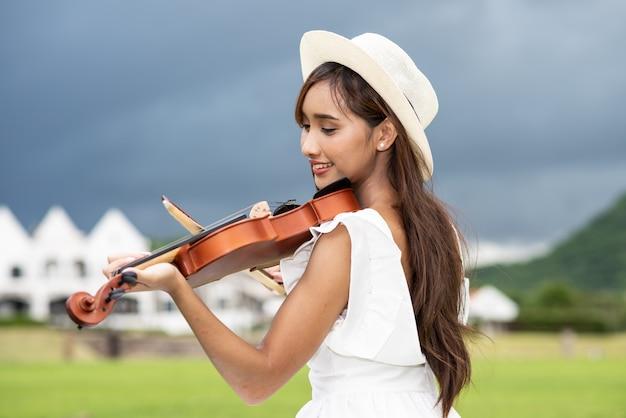 Piękna azjatka z długimi włosami gra na skrzypcach