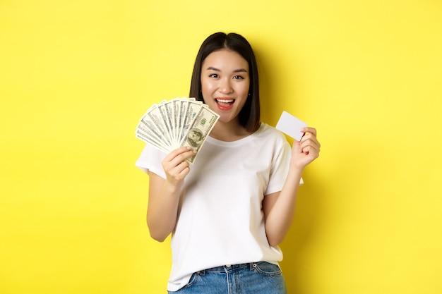 Piękna azjatka z krótkimi ciemnymi włosami, ubrana w białą koszulkę, pokazująca pieniądze w dolarach i plastikową kartę kredytową, stojąca na żółto.