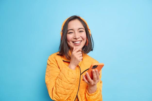 Piękna azjatka z uśmiechem na ustach lubi słuchać świetnej piosenki ze swojej playlisty, używa nowoczesnych bezprzewodowych słuchawek stereo smartfona, trzyma podbródek, nosi pomarańczową kurtkę na niebieskiej ścianie.
