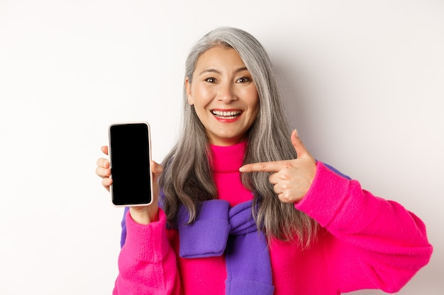 Piękna azjatycka babcia uśmiechając się, wskazując palcem na pusty ekran smartfona, pokazując aplikację mobilną, stojąc na białym.