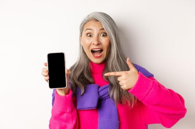 Piękna azjatycka babcia uśmiechnięta, wskazująca palcem na pusty ekran smartfona, wyglądająca na zdumioną, pokazująca aplikację mobilną, stojąca na białym.
