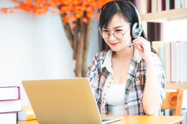 Piękna azjatycka biała kobieta w okularach i słuchawkach z radością korzysta z laptopa do nauki online.