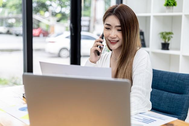 Piękna azjatycka bizneswoman siedząca w swoim pokoju, rozmawiająca ze swoim partnerem przez telefon komórkowy i sprawdzająca dokumenty finansowe, jest kobietą z kadry kierowniczej startującej firmy. zarządzanie finansami.