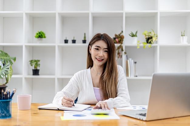 Piękna azjatycka bizneswoman siedzi w swoim gabinecie, sprawdza dokumenty finansowe firmy, jest kobietą dyrektorem startującej firmy. pojęcie zarządzania finansami.