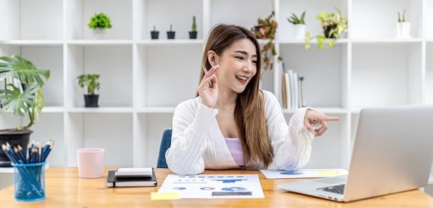 Piękna azjatycka bizneswoman siedzi w swoim prywatnym gabinecie, rozmawia ze swoim partnerem przez wideorozmowę na swoim laptopie, jest kobietą z kierownictwa firmy rozpoczynającej działalność. koncepcja zarządzania finansami