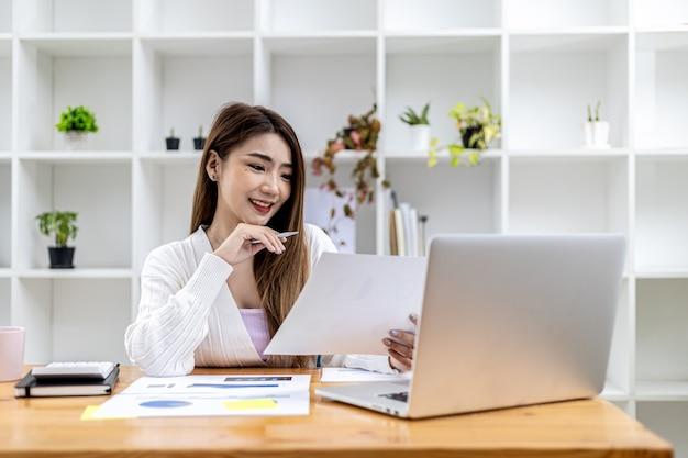Piękna azjatycka bizneswoman siedzi w swoim prywatnym gabinecie, rozmawiając ze swoim partnerem przez laptopa i sprawdzając dokumenty, jest kobietą z kadry kierowniczej startującej firmy. koncepcja zarządzania finansami.