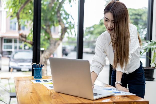 Piękna azjatycka bizneswoman stojąca w pokoju, rozmawia ze swoim partnerem przez komunikator w laptopie, jest kobietą dyrektorem firmy startowej. koncepcja zarządzania finansami