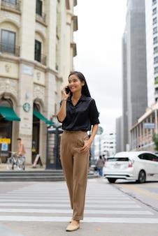 Piękna azjatycka bizneswoman uśmiecha się i rozmawia przez telefon na zewnątrz na ulicy podczas spaceru