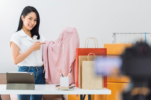 Piękna azjatycka blogerka pokazująca i recenzująca produkt