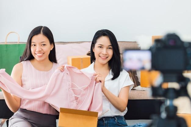 Piękna azjatycka blogerka pokazuje i przegląda produkt odzieżowy