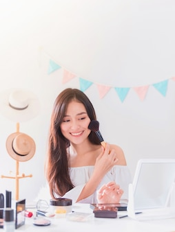 Piękna azjatycka blogerka pokazuje, jak makijażować i używać kosmetyków.