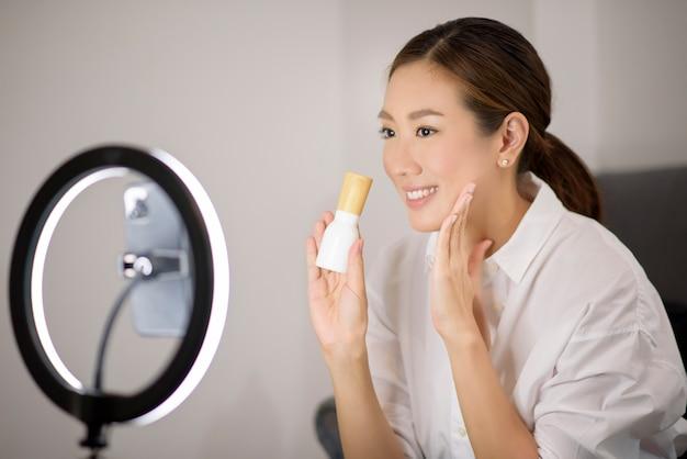 Piękna azjatycka blogerka zajmująca się makijażem transmituje na żywo, jak upiększać makijaż twarzy w swoim domu