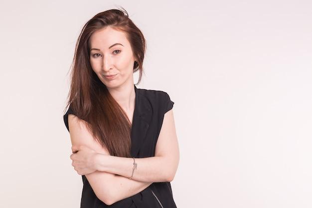 Piękna azjatycka brunetka uśmiechnięta kobieta ze skrzyżowanymi rękami na białym z miejsca na kopię.