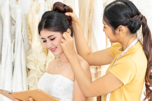 Piękna azjatycka dama wybiera suknię w sklepie z asystentem krawieckim.