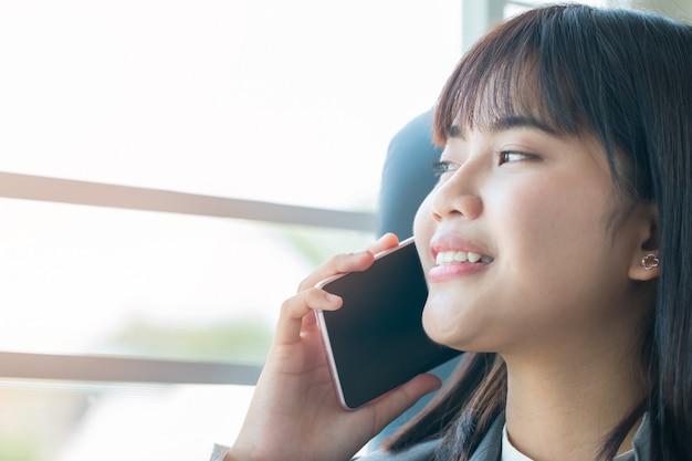 Piękna azjatycka dziewczyna opowiada smartphone i używa laptop dla pracy domowej