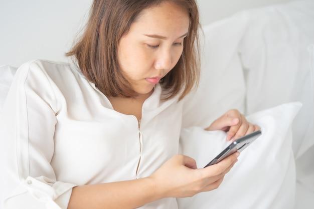 Piękna azjatycka dziewczyna śpi na smartphone. graj na mediach.