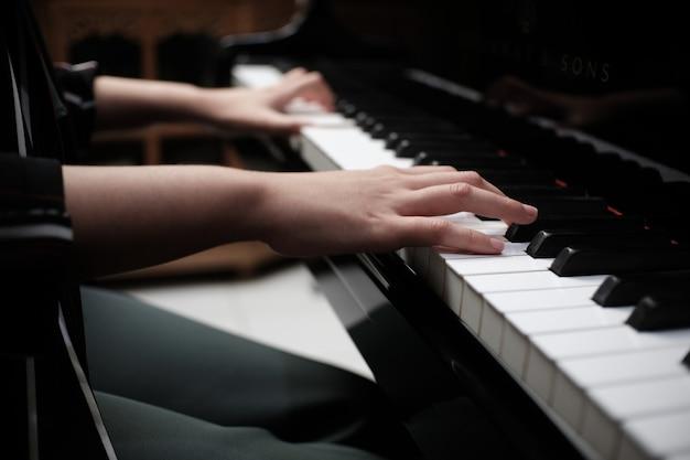 Piękna azjatycka dziewczyna uczy się gry na pianinie.