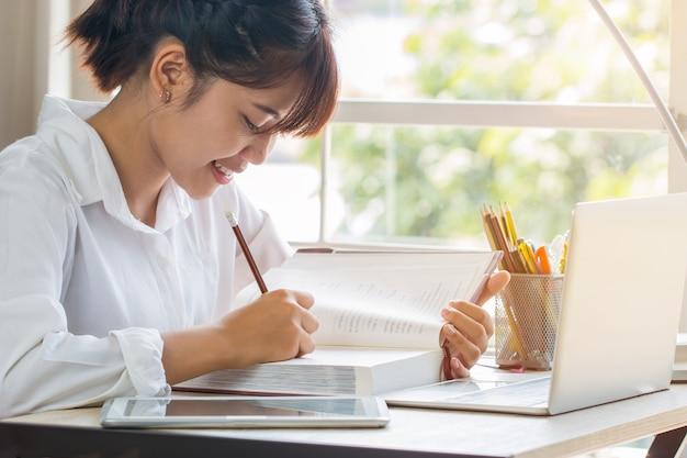 Piękna azjatycka dziewczyna uczy się i pisze w podręczniku lub pracie domowej