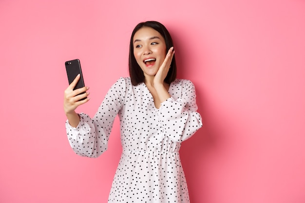 Piękna azjatycka dziewczyna używa aplikacji filtrów fotograficznych i robi selfie na smartfonie, pozuje w ślicznej sukience na różowo.