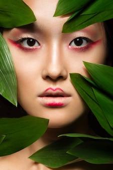 Piękna azjatycka dziewczyna z jaskrawą makijaż sztuką w zielonych liściach.
