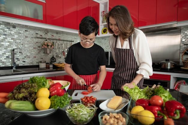 Piękna azjatycka gospodyni domowa w średnim wieku 40 lat ubrana w fartuch stojący w nowej, czerwonej kuchni i uczy syna 10 lat, jak przygotowywać składniki do mieszania różnych sałatek warzywnych.