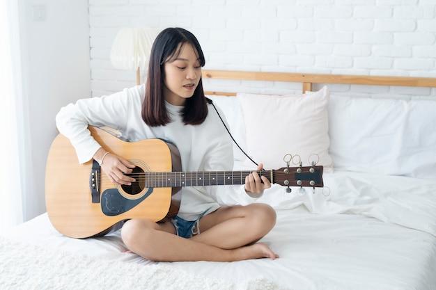 Piękna azjatycka kobieta bawić się gitarę na łóżku w domu